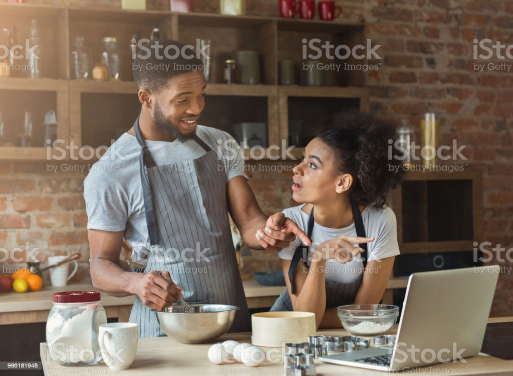 African-american couple cooking pastry with recipe on laptop stock photo