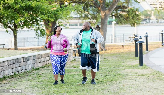 istock African-American couple exercising, power walking 1047628836