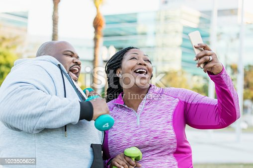 istock African-American couple exercising, taking selfie 1023505622
