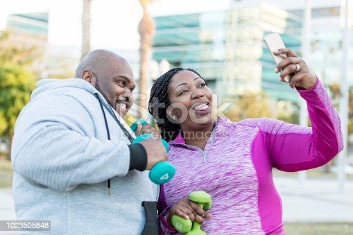 istock African-American couple exercising, taking selfie 1023505848