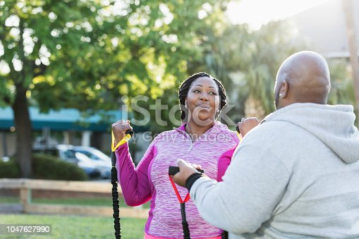 istock African-American couple exercising with resistance bands 1047627990
