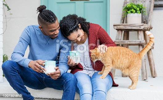 A young African-American couple hanging out together, drinking coffee on the front steps of their home, relaxing and petting a cat.