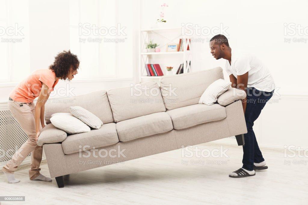 Couple afro-américain infligeant canapé maison neuve - Photo