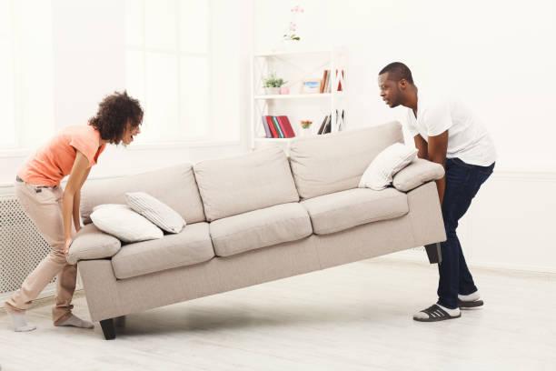 couple afro-américain infligeant canapé maison neuve - ameublement photos et images de collection
