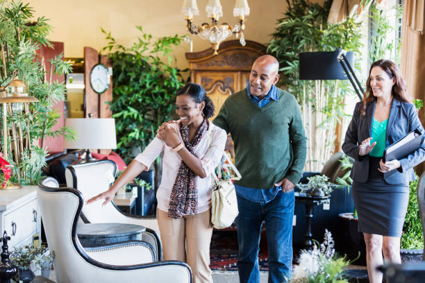 African-American couple shopping in furniture store An African-American couple, the woman in her 30s and the man in his 40s, shopping in a furniture store, being helped by a saleswoman or interior designer. showroom stock pictures, royalty-free photos & images