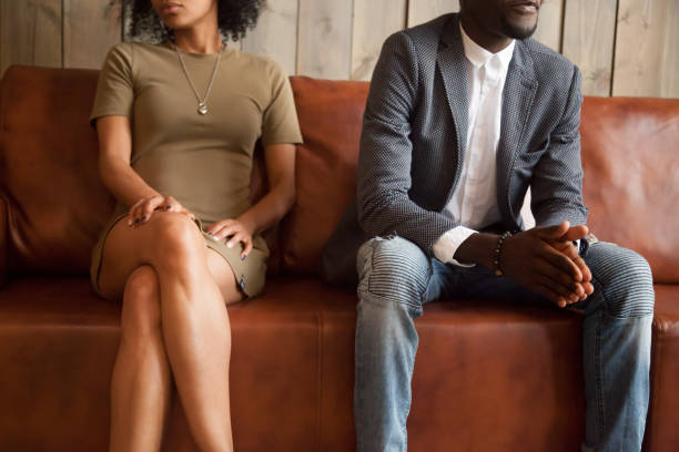 african-american couple sitting on couch after quarrel, bad relationships concept - rudeness stock pictures, royalty-free photos & images