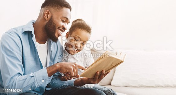 istock African-american dad and daughter reading book together 1152640424
