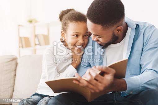 istock African-american dad and daughter spending time, reading book 1152640394