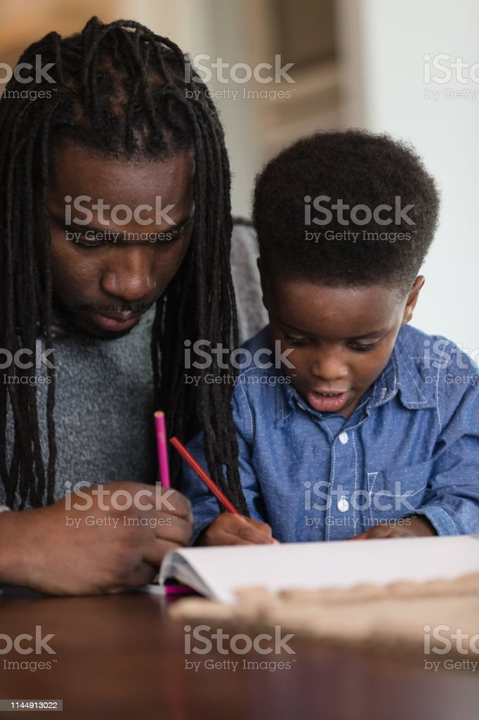 A cute preschool-age African American boy sits on his dad\'s lap while...