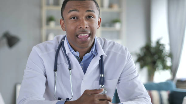 African-American Doctor Talking with Patient, Video Chat stock photo