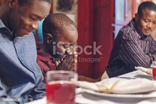 istock African-american doing prayer during thanksgiving dinner 1055904282
