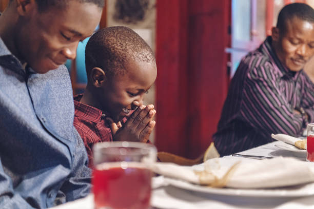 African-american doing prayer during thanksgiving dinner stock photo