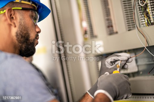 African-American electrician with a hardhat and protective eyewear stripping a wire while wearing protective gloves.