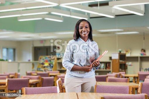 istock African-American elementary school teacher in library 1138226573