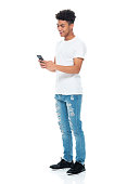 istock African-american ethnicity boys standing in front of white background wearing t-shirt and using smart phone 1208644128