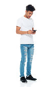 istock African-american ethnicity boys standing in front of white background wearing t-shirt and using smart phone 1208644176