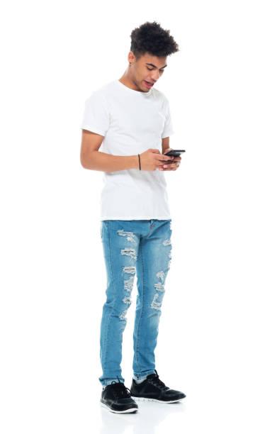 Afroamerikanische Ethnizität Jungen stehen vor weißem Hintergrund tragen T-shirt und mit Smartphone – Foto