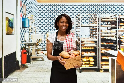 istock African-american ethnicity female baker preparing food at the bakery in front of merchandise in the store wearing apron and holding basket 1211472691