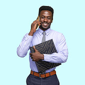 istock African-american ethnicity male business person standing in front of colored background and holding note pad and using smart phone 1208834677