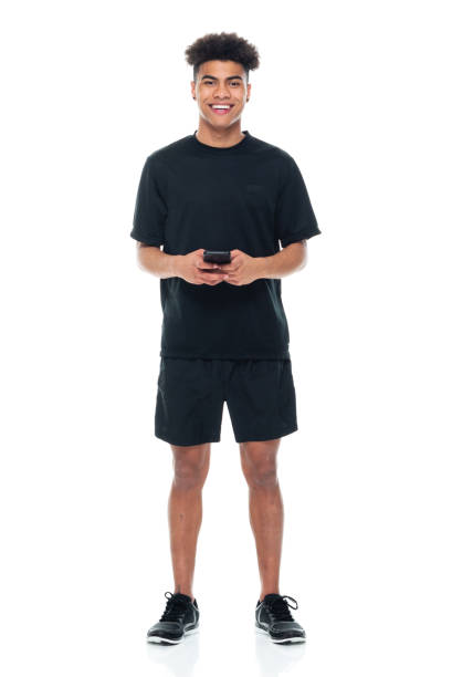African-american ethnicity male standing in front of white background wearing sports shoe and using mobile phone stock photo