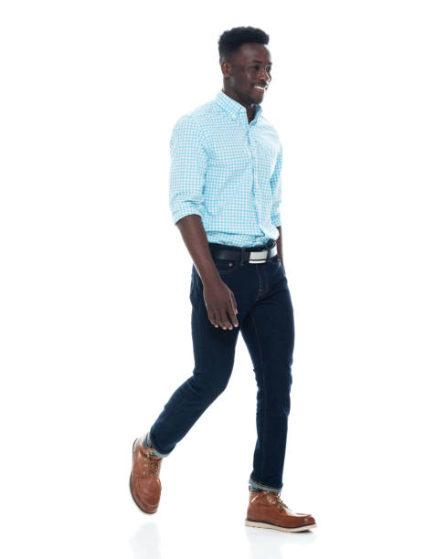 African-american ethnicity male walking in front of white background wearing jeans stock photo