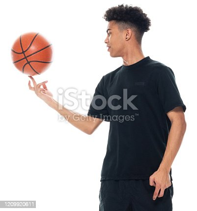 One person of aged 18-19 years old with curly hair african-american ethnicity teenage boys spinning in front of white background wearing shorts who is laughing and holding basketball - ball and using sports ball