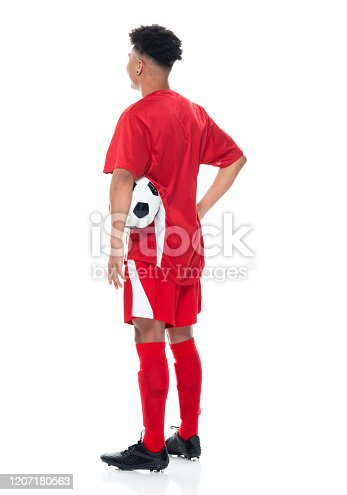istock African-american ethnicity young male athlete standing in front of white background wearing soccer uniform and holding soccer ball and playing soccer - sport and using sports ball 1207180563