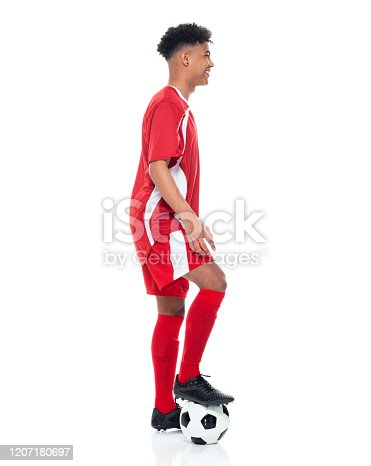 istock African-american ethnicity young male athlete standing in front of white background wearing soccer uniform and holding soccer ball and playing soccer - sport and using sports ball 1207180697