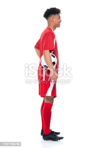 istock African-american ethnicity young male athlete standing in front of white background wearing soccer uniform and holding soccer ball and playing soccer - sport and using sports ball 1207180760