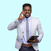 istock African-american ethnicity young male business person standing in front of colored background wearing jacket and using digital tablet 1209148706