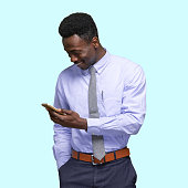 istock African-american ethnicity young male businessman standing in front of colored background wearing pants and using mobile phone 1209148821