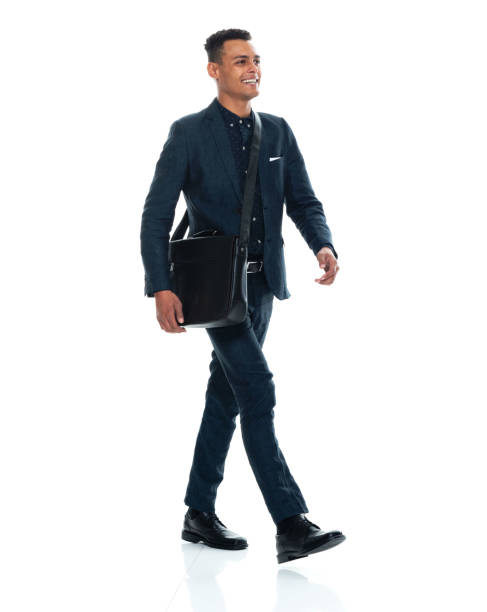 African-american ethnicity young male businessman walking in front of white background wearing satchel - bag and holding bag stock photo