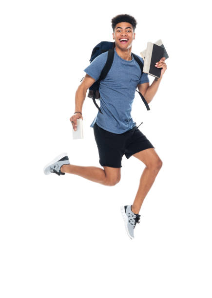 African-american ethnicity young male university student jumping wearing backpack and holding bag stock photo