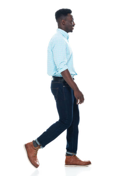 African-american ethnicity young male walking in front of white background wearing jeans stock photo