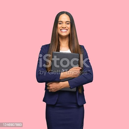 istock African-american ethnicity young women manager standing in front of colored background wearing skirt and using laptop 1246907883