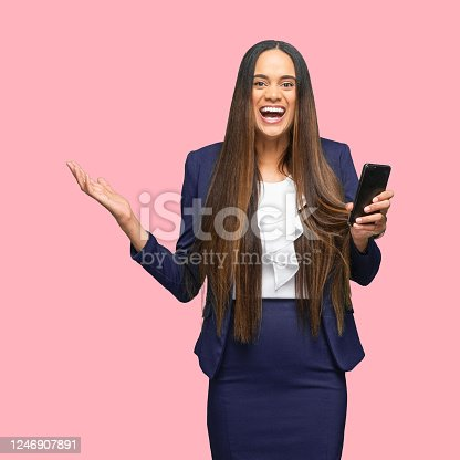 istock African-american ethnicity young women manager standing in front of colored background wearing jacket and using mobile phone 1246907891