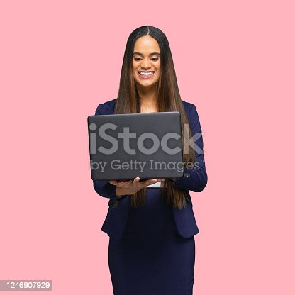 istock African-american ethnicity young women manager standing in front of colored background wearing skirt and using computer 1246907929