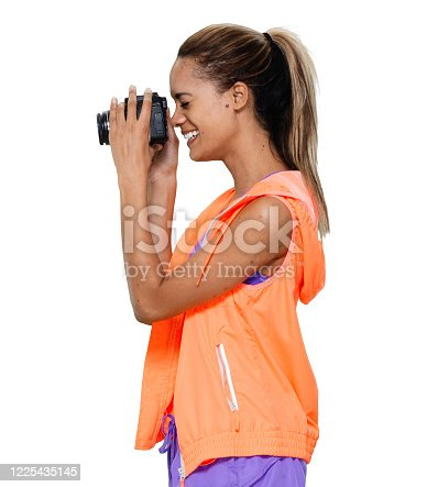 istock African-american ethnicity young women photographer standing in front of white background wearing sports bra and holding camera 1225435145