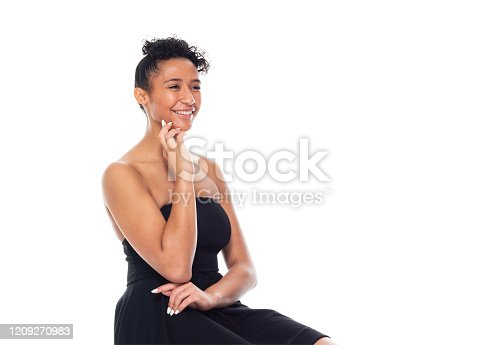 Side view of aged 20-29 years old who is beautiful african-american ethnicity young women resting in front of white background wearing dress who is smiling