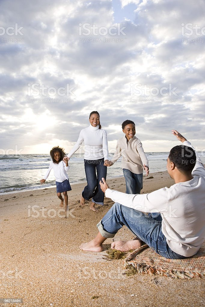 African-American family running to dad on beach royalty-free stock photo