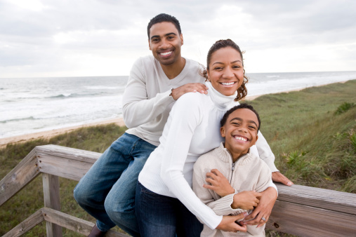 istock African-American family smiling and hugging at beach 118888541