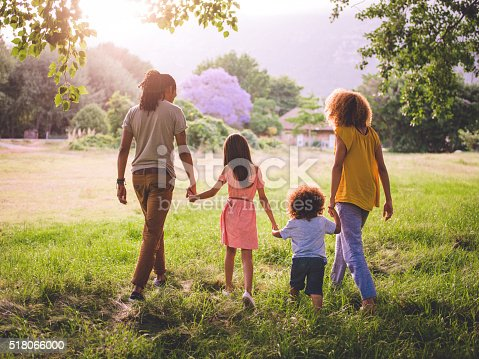 518064982 istock photo African-american family taking a walk in a beautiful park 518066000