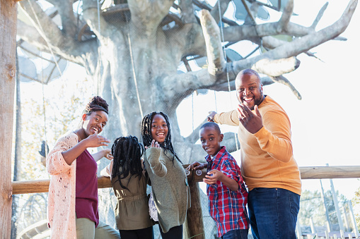 An African-American family with three children visiting the zoo, standing in front of a large tree in the primate exhibit, smiling at the camera. The boy is 10 years old and the girls are 7 and 9. The parents are in their 30s.
