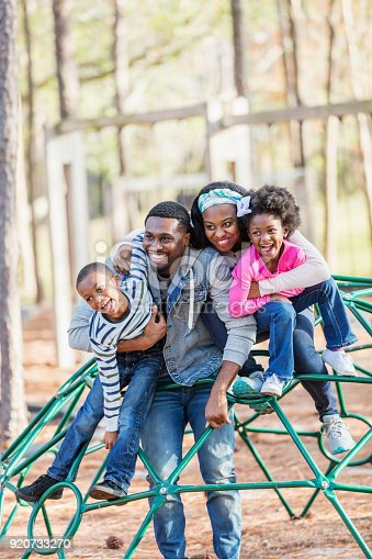 istock African-American family with two children on playground 920733270