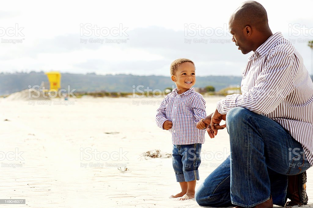 African-American father and son on the beach stock photo
