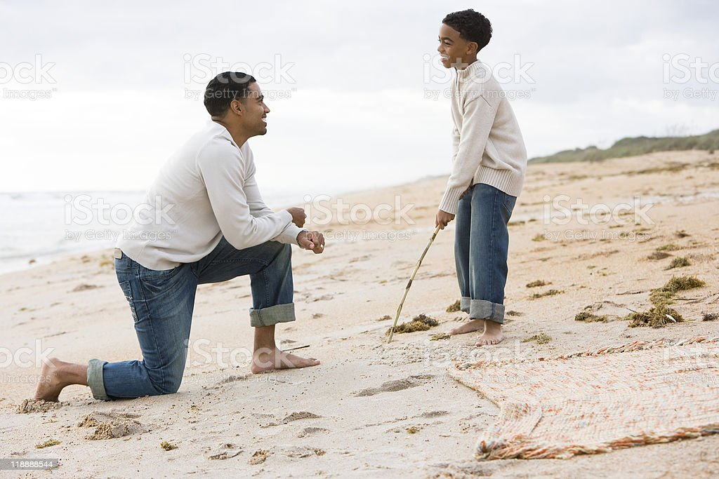 African-American father and son playing on beach royalty-free stock photo