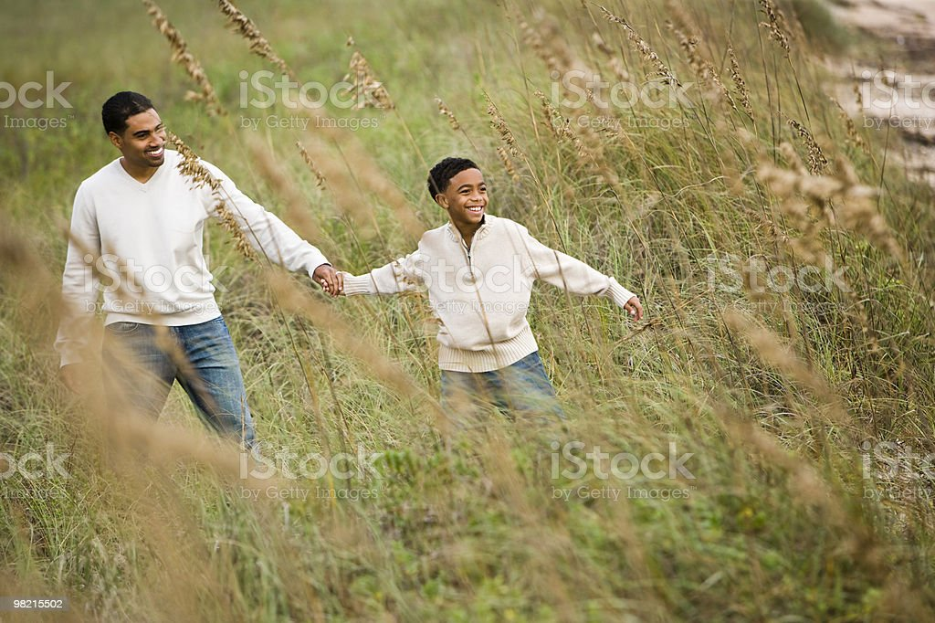 African-American father and son walking through grass at beach royalty-free stock photo