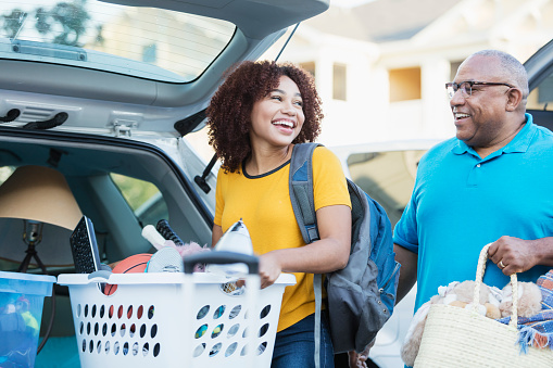 A mature African-American man helping his daughter relocate, perhaps into an apartment or college dorm.  They are in a parking lot unloading their cars. The young woman is carrying a laundry basket filled with her belongings.