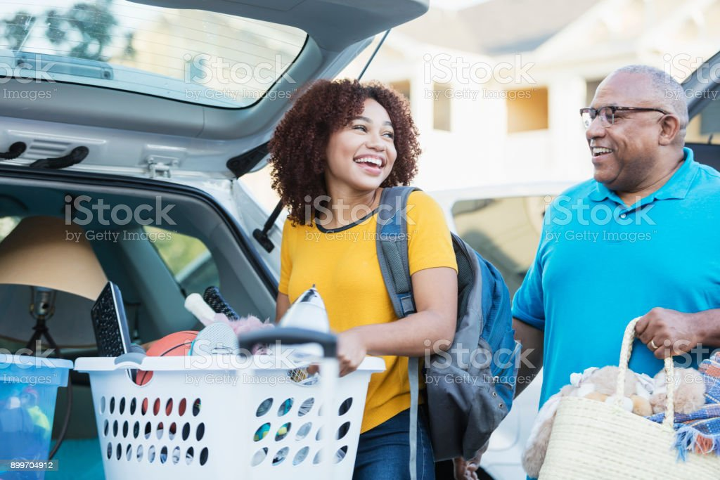 African-American father helping daughter move stock photo
