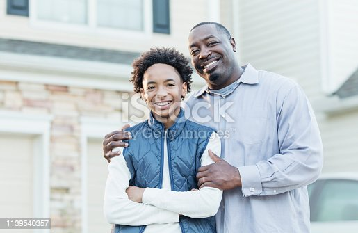 istock African-American father, mixed race son in front of home 1139540357
